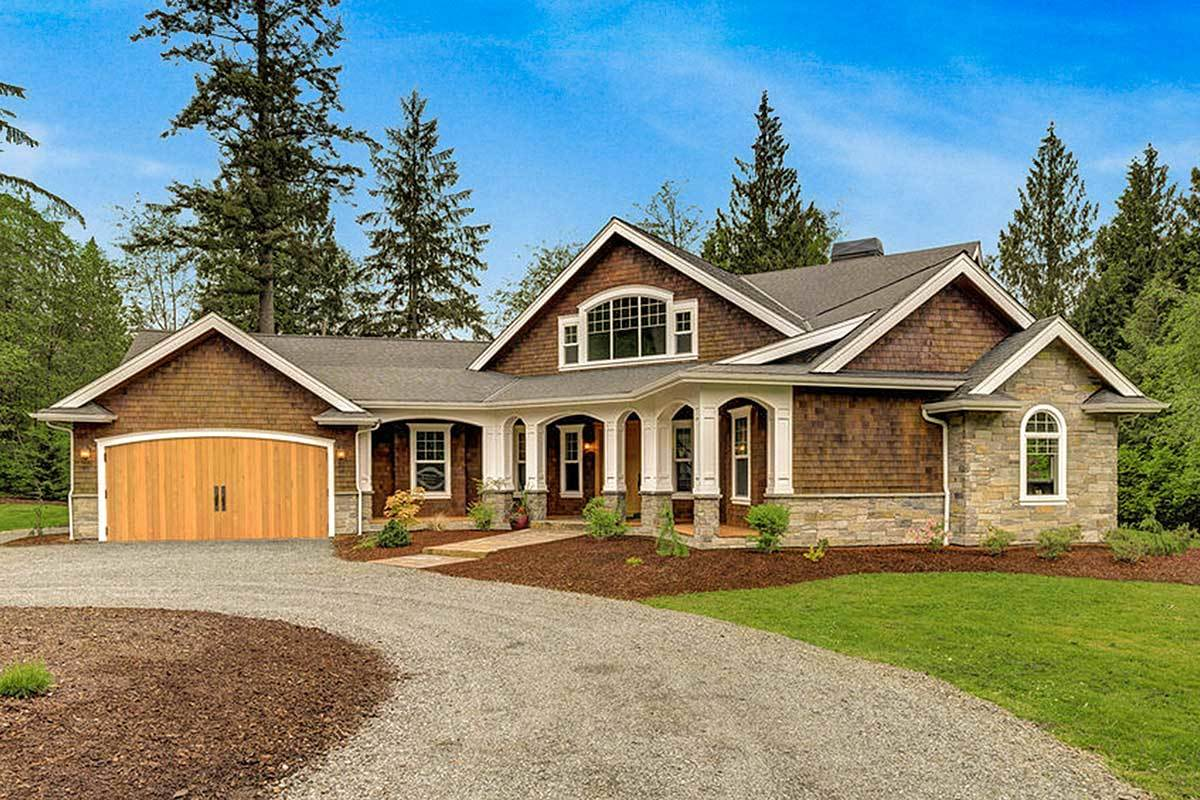 A circular gravel driveway accentuated with green lawn and a few, small shrubs complement the craftsman-style home.