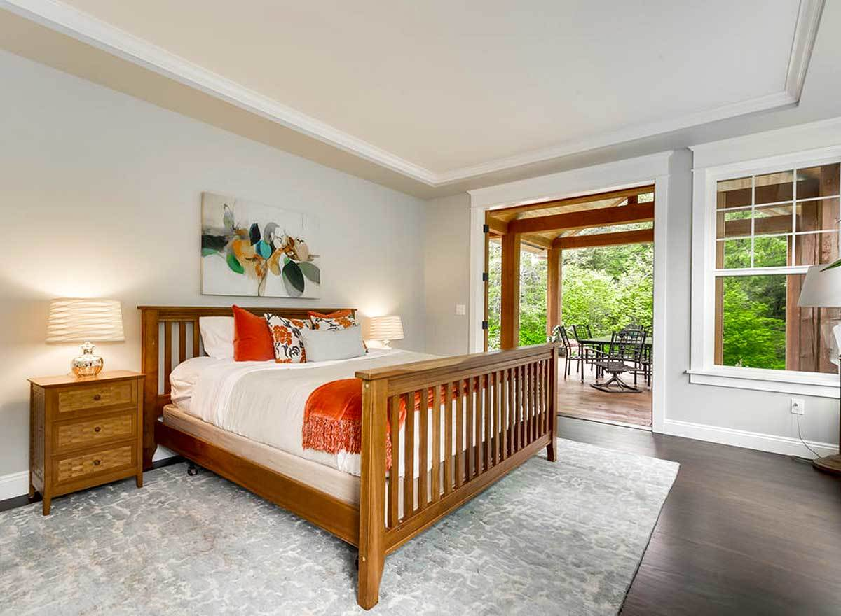 Primary bedroom with light gray walls and tray ceiling softened by a cozy wooden bed and matching nightstands. It extends onto a private porch framed with wooden beams.
