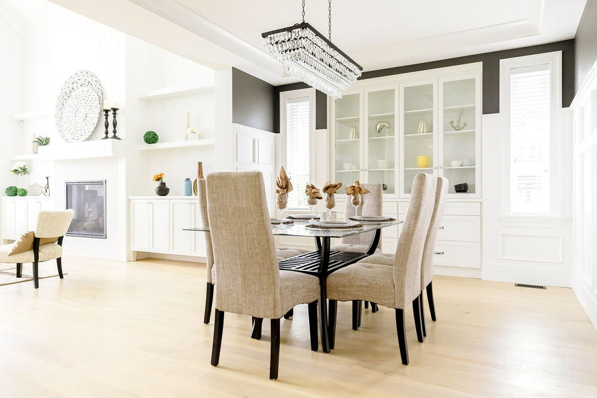 The light and airy feel in this dining room is enhanced by white walls and built-ins, light hardwood flooring, and glass panels from the tables and cabinets that reflect light and dispersed it across the room.