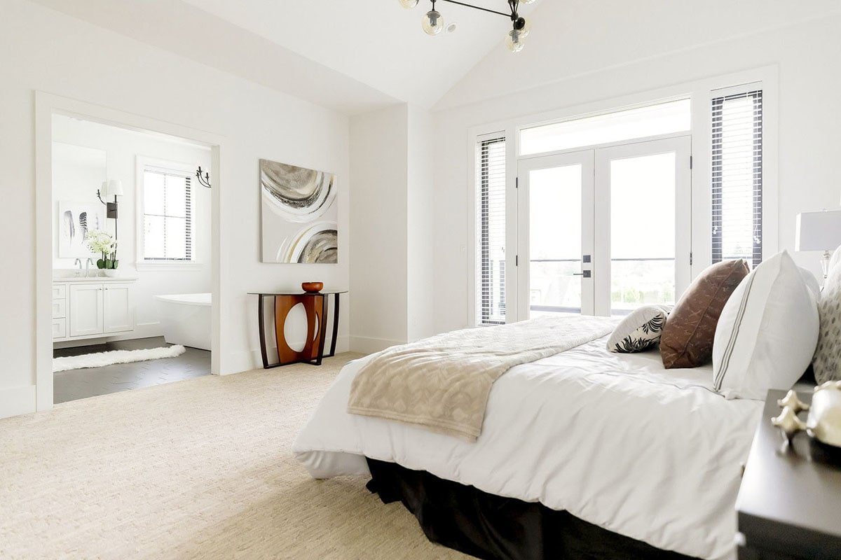This primary bedroom is bright and airy enhanced by white walls, beige carpet flooring, and a french door surrounded by transom window and sidelights.