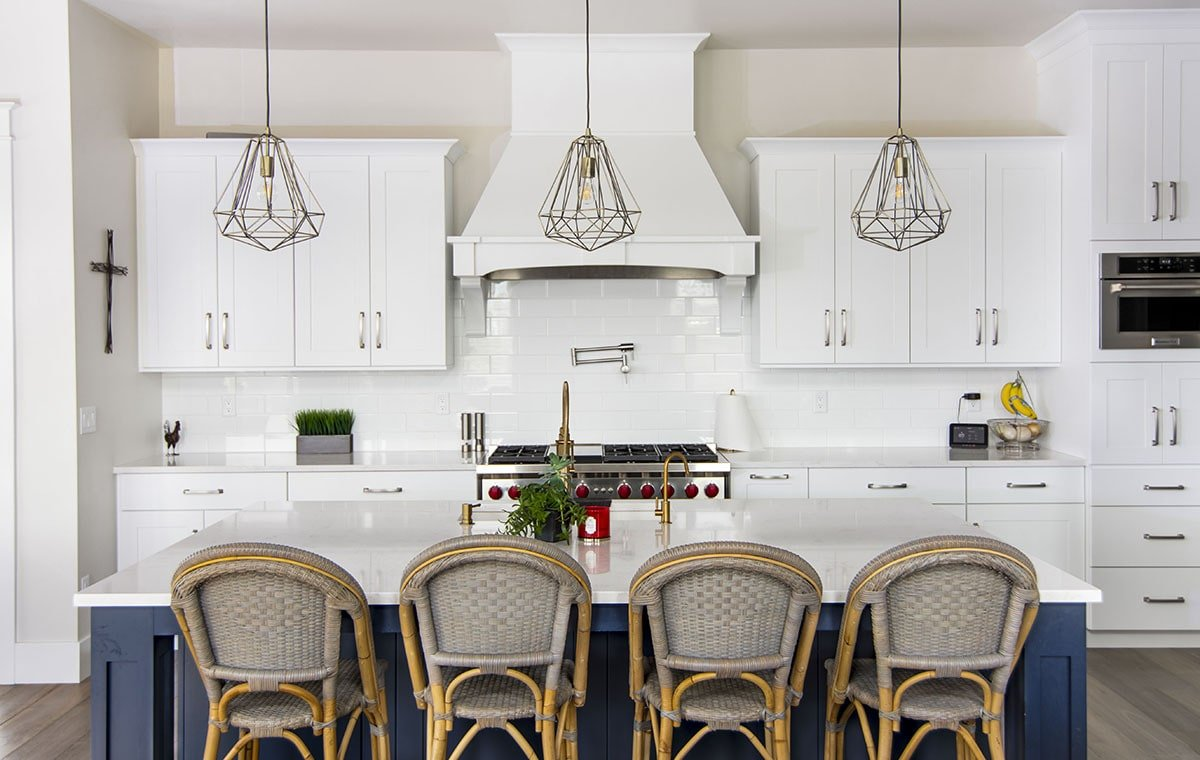 This kitchen features white cabinetry, subway tile backsplash, and a deep blue island complemented with geometric pendants and rustic counter chairs.