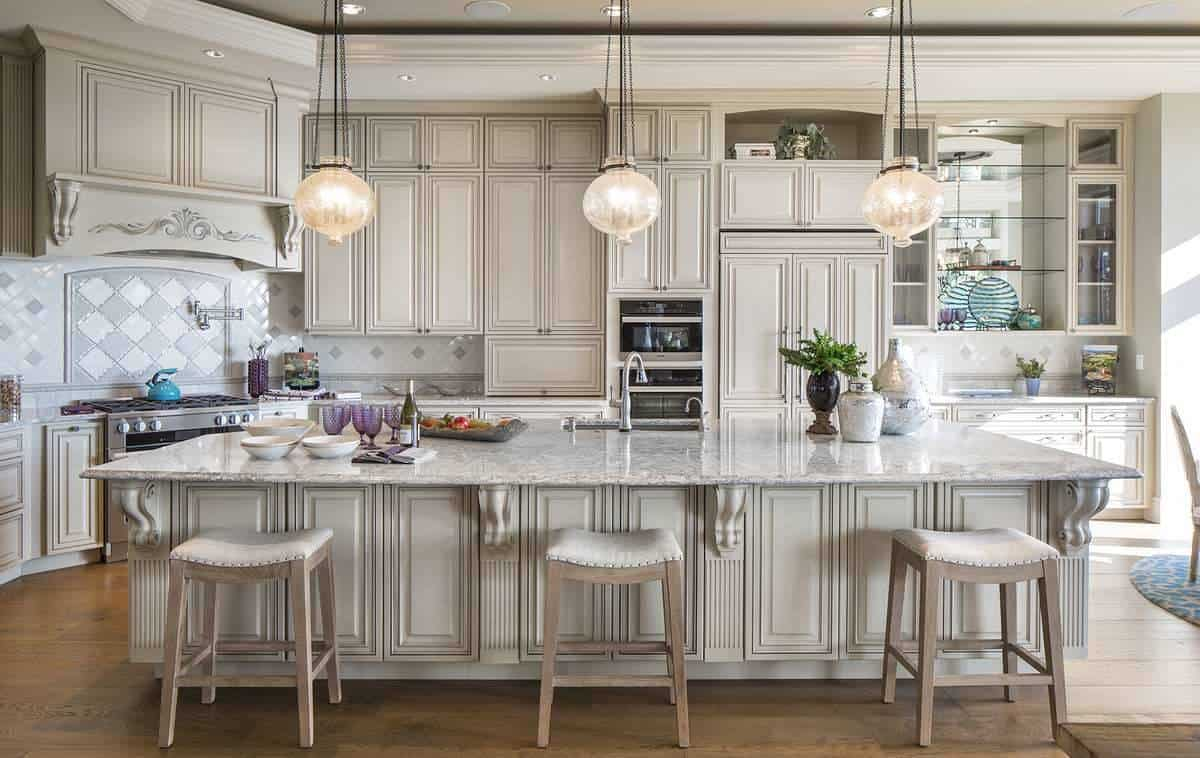 The kitchen features taupe cabinetry and a granite top island bar lined with cushioned stools and glass globe pendants. The wooden legs of the stools go well with the darker tone of the hardwood flooring.
