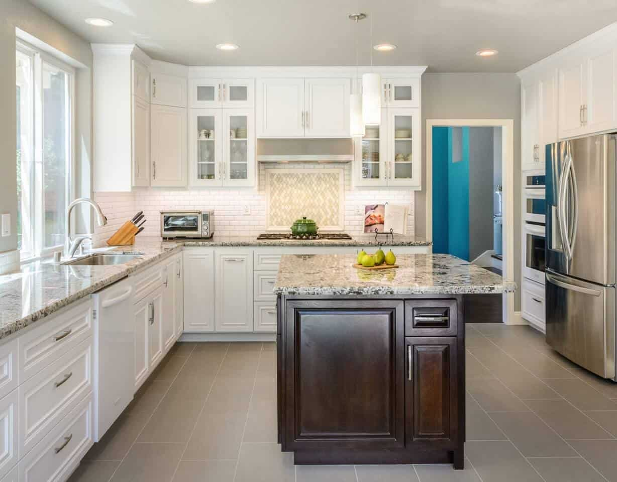 Transitional kitchen features white cabinetry and oven contrasted with a dark wood central kitchen island topped with a marble counter.