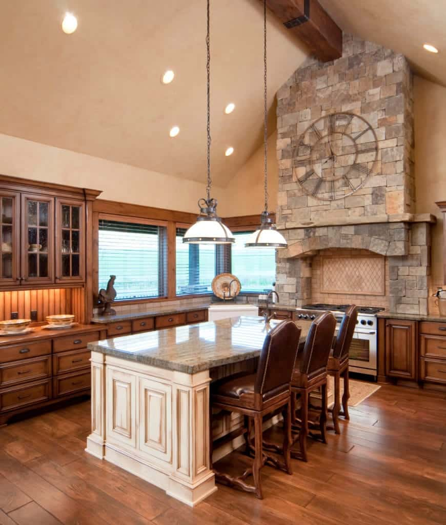 Rustic kitchen boasts wood cabinetry and a range alcove clad in stone bricks. It has a white central island illuminated by dome pendants and recessed lights mounted on the cathedral ceiling lined with wood beam.