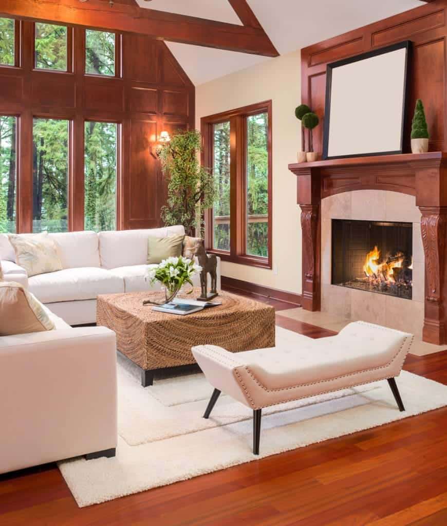 Cozy living room with redwood wall and fireplace complementing with the hardwood flooring topped by a white shaggy rug. It includes white sectionals and a tufted bench paired with a wicker coffee table.