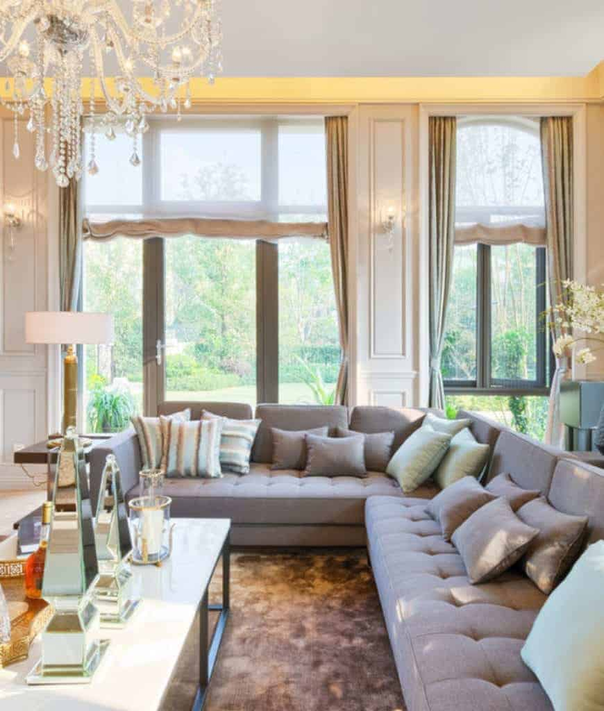 Fresh living room with gray tufted sofa and a metal coffee table lighted by a fancy chandelier along with natural light that flows through the full height windows.