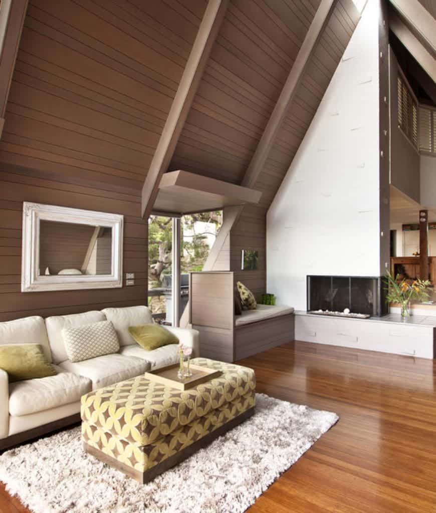 Cozy living room with wood plank vaulted wall and rich hardwood flooring topped by a shaggy rug. It has a beige sectional paired with a diamond pattern ottoman and a sleek fireplace adjacent to the built-in seat nook.