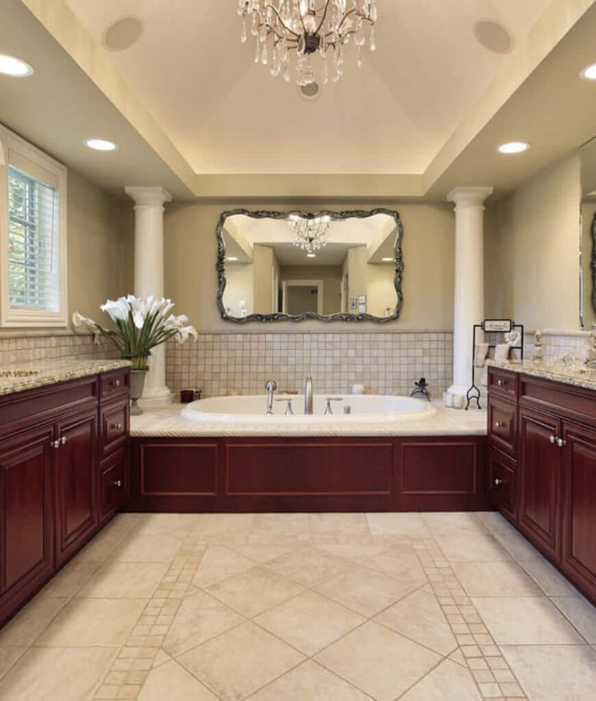 Stylish primary bathroom decorated with ornate mirror mounted above the drop in bathtub that's lined with white columns. It is lighted by a crystal chandelier that hung from the tray vaulted ceiling.