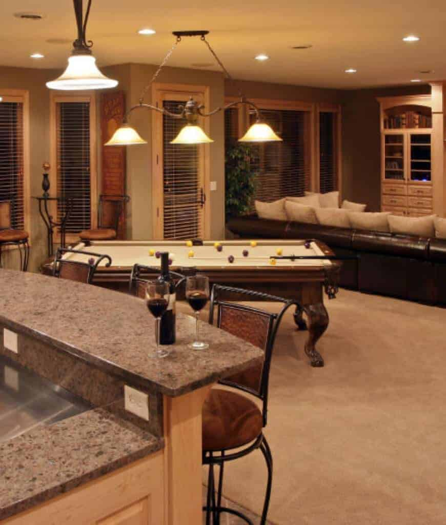Well-lit man cave features a pool table in between the living space and bar area showcasing marble countertop lined with metal bar chairs. It is illuminated by vintage pendants and recessed ceiling lights.