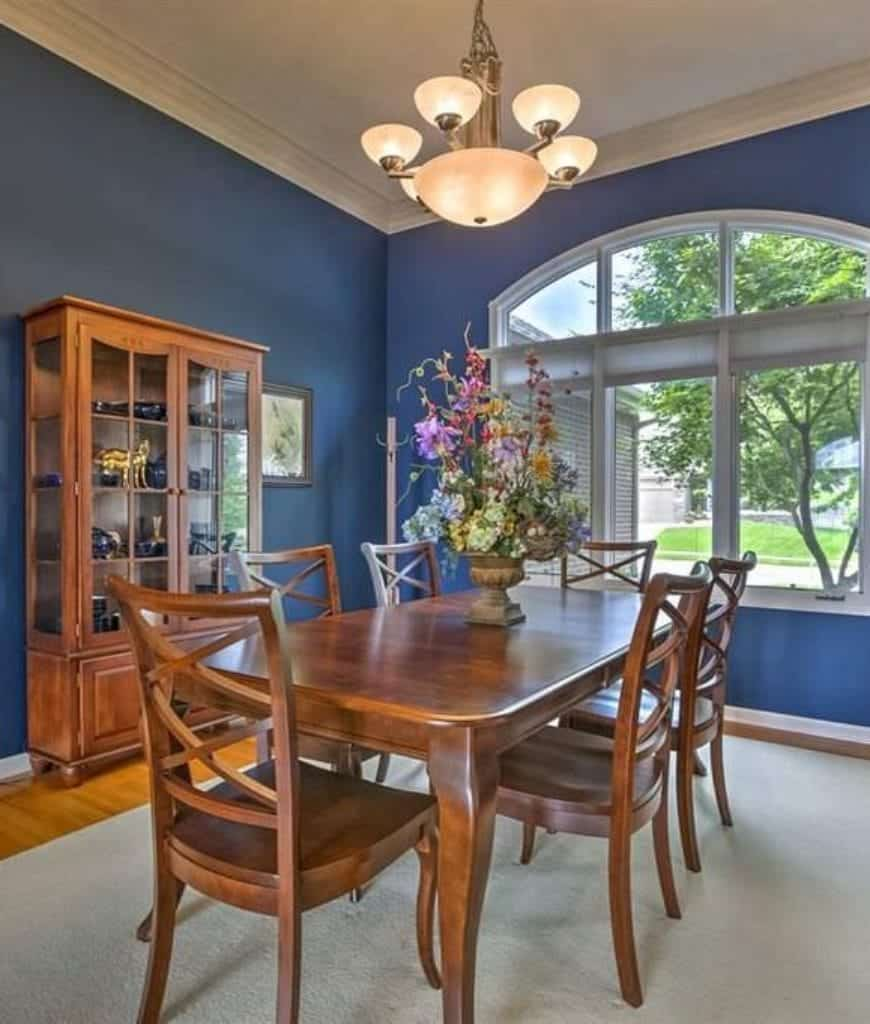 A wooden display cabinet filled with blue violet dinnerware sits across the wooden dining set in this dining room with arched window and a beige rug that lays on hardwood flooring.