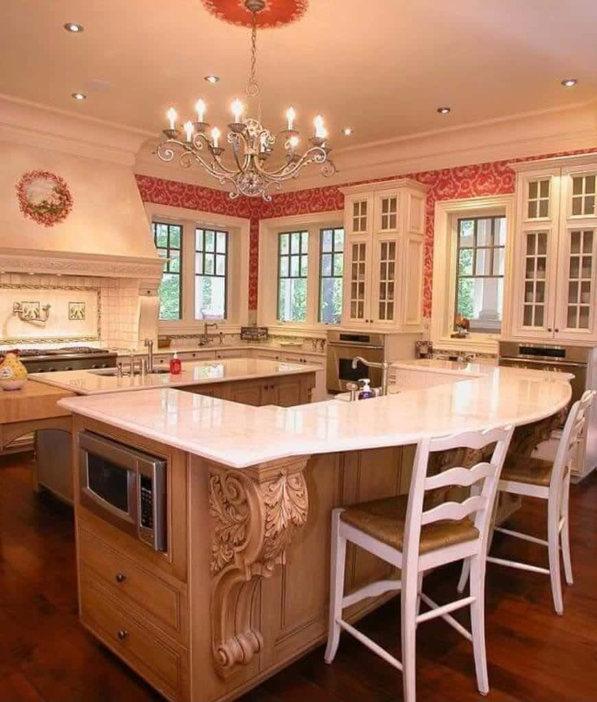 Gorgeous kitchen clad in lovely pink wallpaper offers white cabinetry and double kitchen islands lighted by a chrome candle chandelier and recessed ceiling lights.