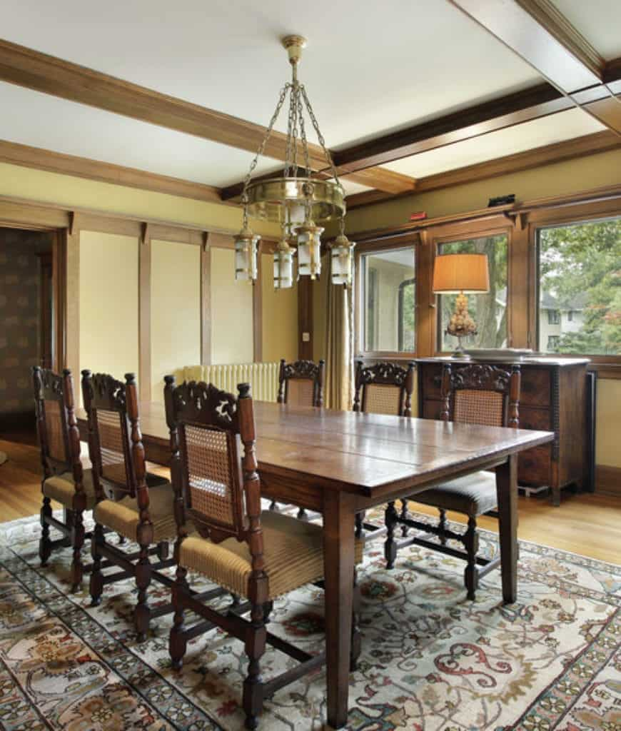This dining set features hardwood flooring and coffered ceiling with a hanging brass chandelier. It includes a wood plank dining table paired with tan cushioned chairs.