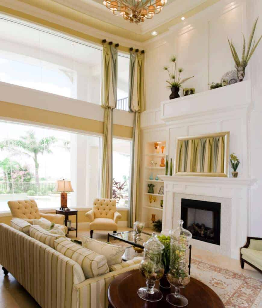 Natural light streams through the panoramic windows in this living room with green striped sofa that complements with the curtains and wall art above the white fireplace.