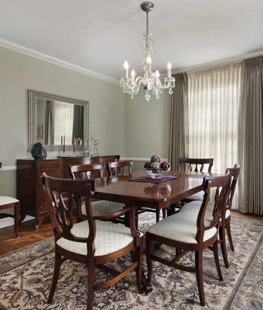 Sophisticated dining room designed with a crystal chandelier and ornate framed mirror mounted above the wooden buffet table that complements with the dining set on a patterned rug.