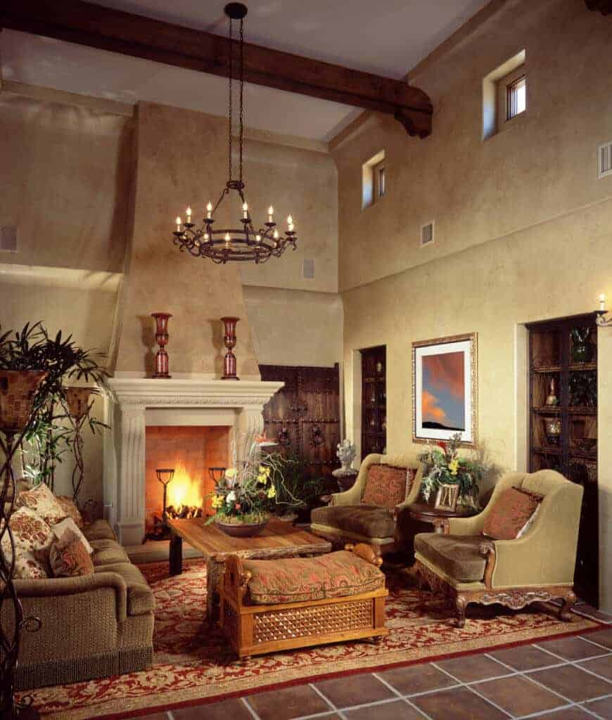 Spanish style living room with cozy seats and a wooden coffee table that faces the brick fireplace. It includes a wrought iron chandelier and a red area rug that lays on terracotta flooring.