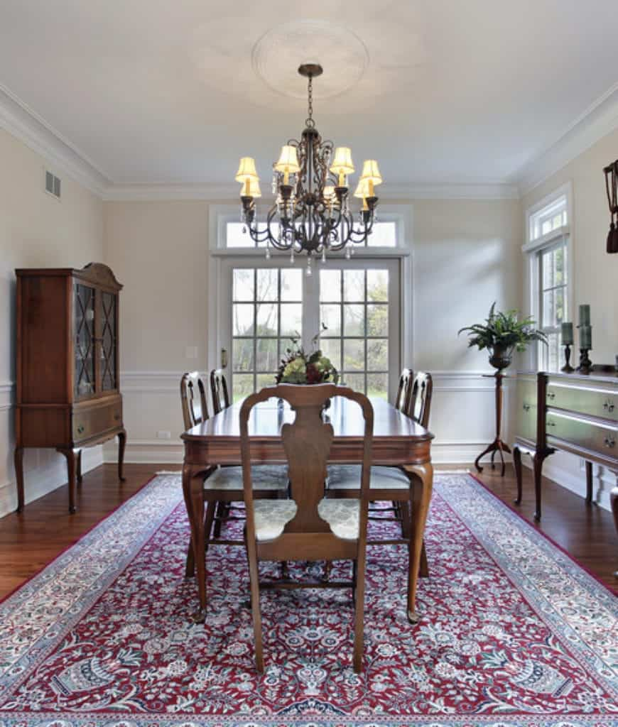 A vintage chandelier hangs over the wooden dining set in this dining room with a classic red bordered rug that lays on the hardwood flooring.