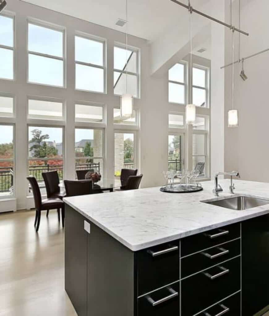 Modern kitchen with smooth hardwood flooring and a towering ceiling with hanging track and pendant lights. It includes a black kitchen island and lovely dining set by the glazed windows overlooking a serene outdoor view.
