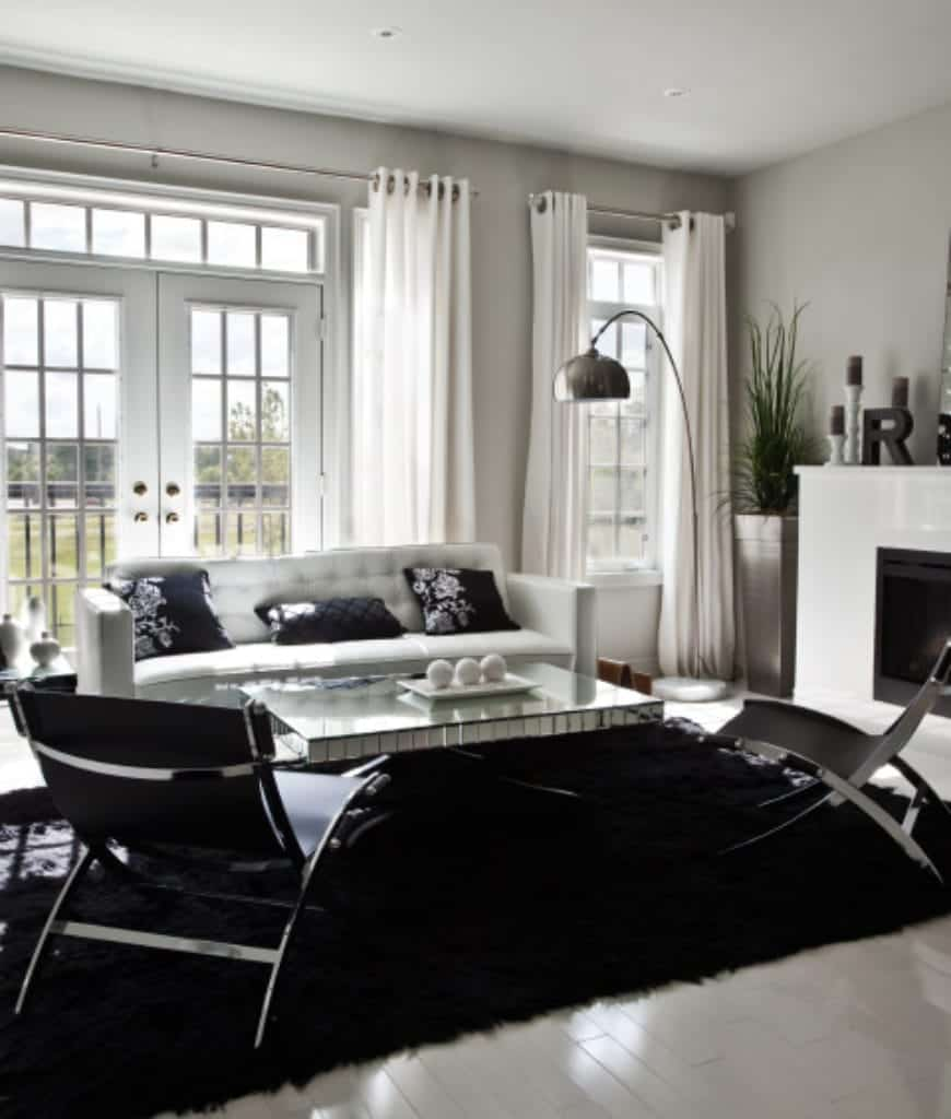 Modern living room boasts tiled flooring topped with a black shaggy rug and framed glass windows covered with white draperies. It has metal chairs and white tufted sofa filled with navy blue floral pillows.