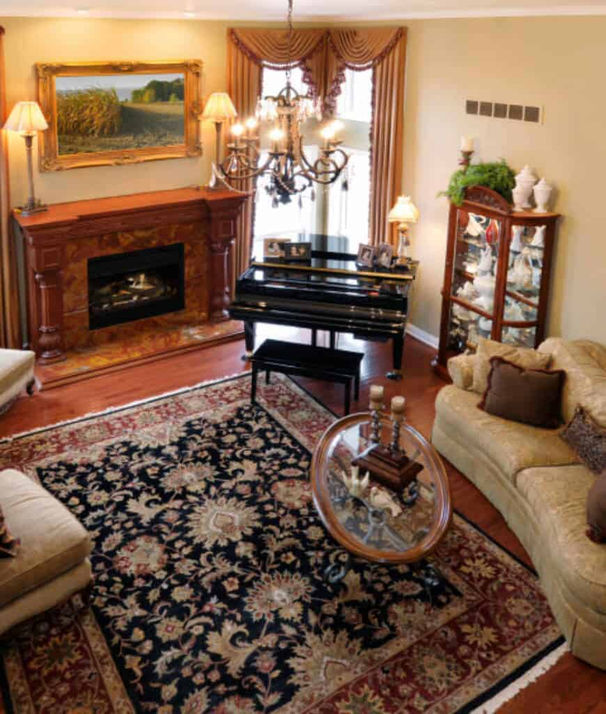Cozy living room decorated with a framed wall art that hung above the fireplace lighted by table lamps and chandelier. There's a baby grand piano by the full height windows covered with classy valences.