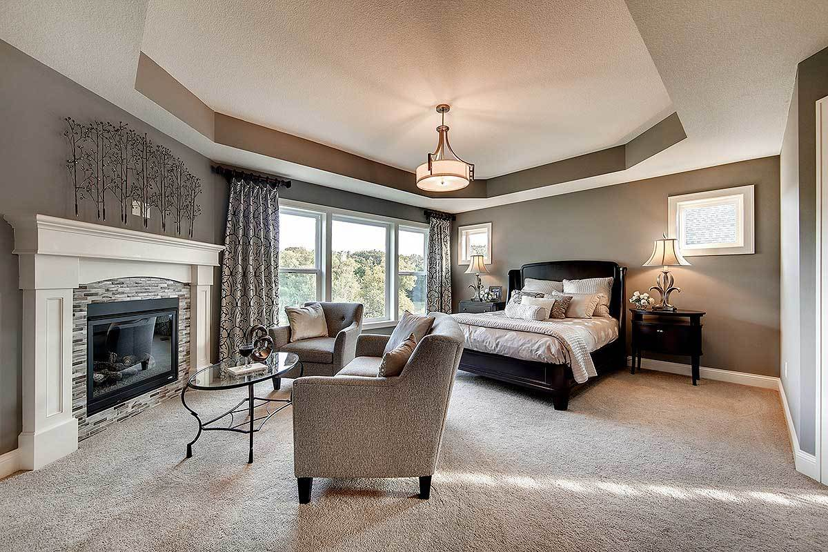 This elegant and luxurious bedroom has a large tray ceiling that blends well with the gray walls and patterned curtains. These gray tones augment the large black frame of the bed as well as its bedside drawers bearing lamps. At the foot of the bed is a cozy sitting area with a large fireplace.
