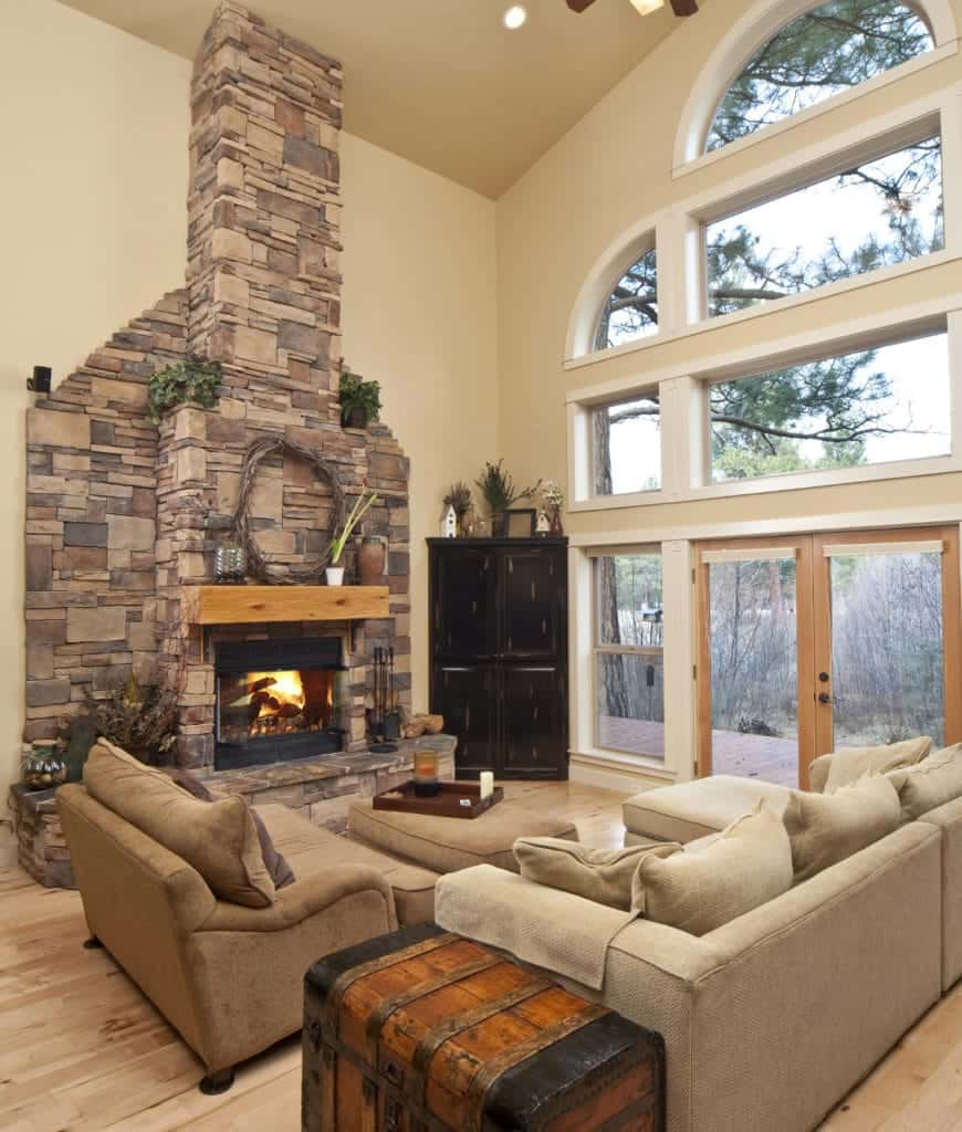 Fluffy brown and beige pillows lay on the sofas in this living room showcasing a stone fireplace and glass paneled windows where you can have a view of the fresh outdoor.