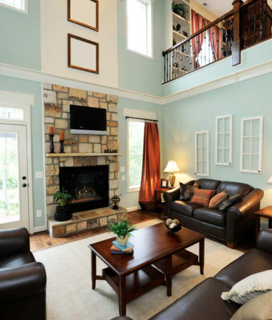 Sky blue living room accented with a stone fireplace that's lined with a wooden mantel. It offers a black leather sofa set and a wooden coffee table that sits on a jute rug.