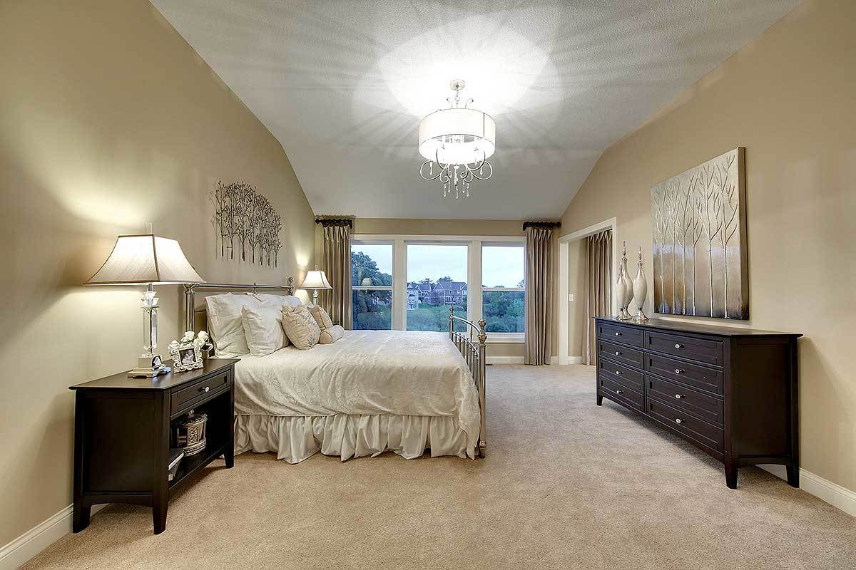 The lovely white cove ceiling of this bedroom is complemented by the beige walls and the natural lights coming in from the glass wall on the far end. These serve as nice background for the metal-frame bed and the surrounding wooden dressers.
