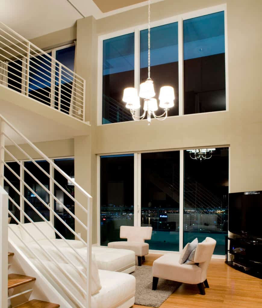 Modern living room with white sleekseats and on a gray shaggy rug illuminated by a chandelier that hung from the high ceiling.