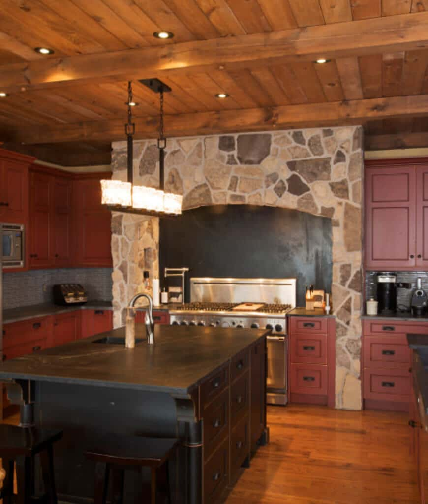 Red kitchen accented with a stone range alcove showcases a black breakfast bar lighted by a linear chandelier that hung from the wood plank ceiling.
