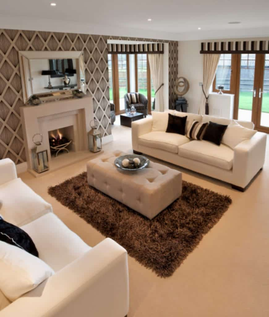Gorgeous living room with white sectionals and tufted ottoman facing the fireplace fixed to the diamond pattern accent wall.