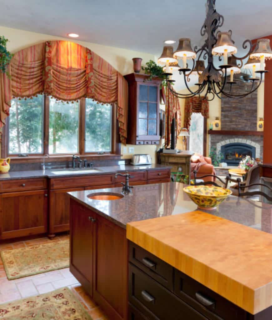 This kitchen features terracotta flooring and arched window dressed in charming striped valence. It includes a shade chandelier that hung over the kitchen island topped with a round sink and yellow decorative bowl.