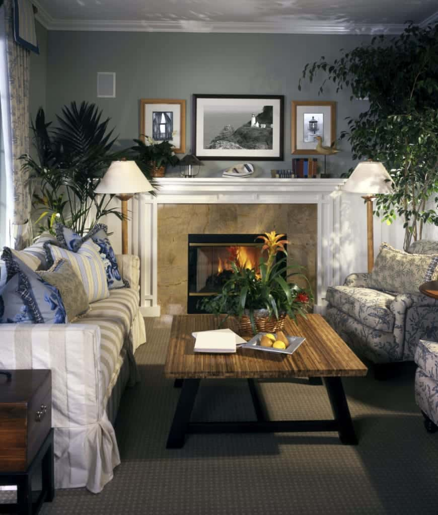 Tropical living room decorated with lovely framed walls arts that hung above the fireplace with beige marble surround tiles. It includes floral armchairs and a wooden coffee table along with a striped skirted sofa filled with charming blue pillows.