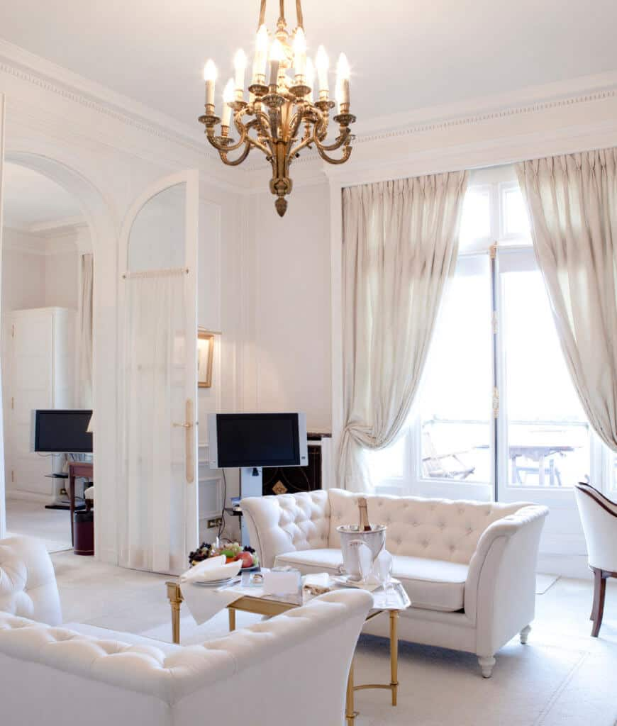 Gorgeous white living room showcases facing tufted couches and a brass coffee table that complements with the candle chandelier.