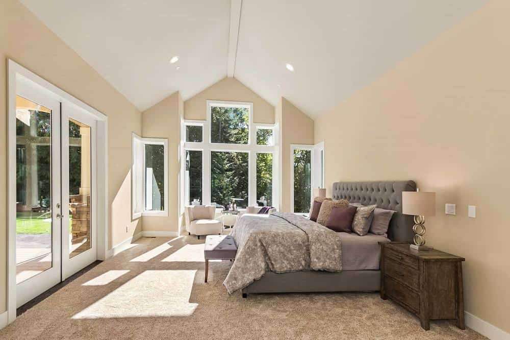 The gray cushioned bed frame of this bedroom stands out against the beige walls and white cathedral ceiling. These match well with the cushioned chairs placed by the tall windows.