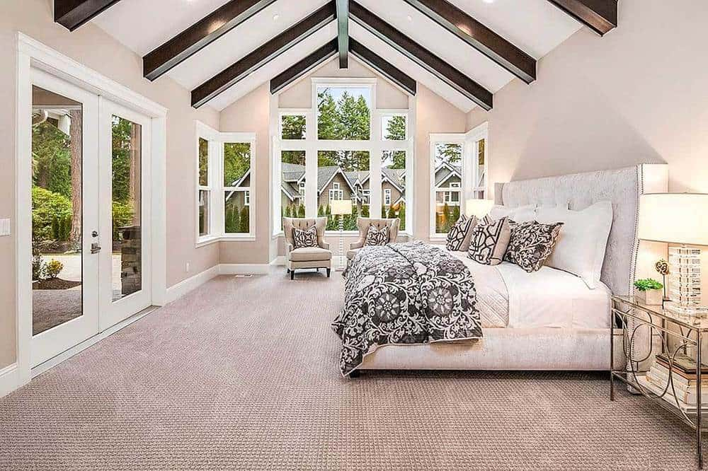 The white cathedral ceiling of this bedroom is contrasted by the dark exposed wooden beams. The white cushioned headboard of the bed complements the beige walls that are brightened by the large set of windows on the side.