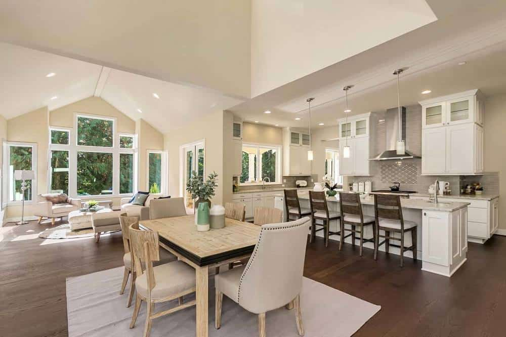 This is an informal dining area just a few steps from the kitchen and the living room on the same dark hardwood flooring and tall beige ceiling. It stands out against the dark flooring with its light wooden dining table, light gray chairs, and light gray area rug.
