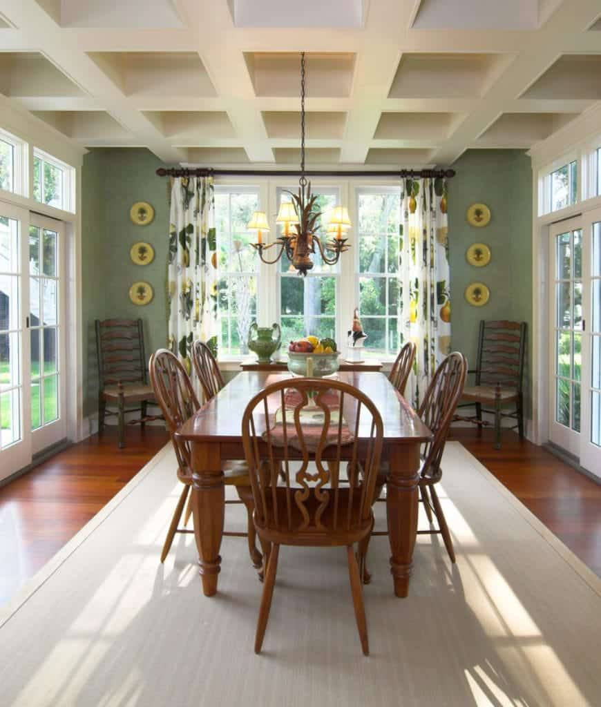 Charming dining room surrounded with floor to ceiling framed windows that bring plenty of natural light in. It has coffered ceiling and rich hardwood flooring topped by a smooth area rug.