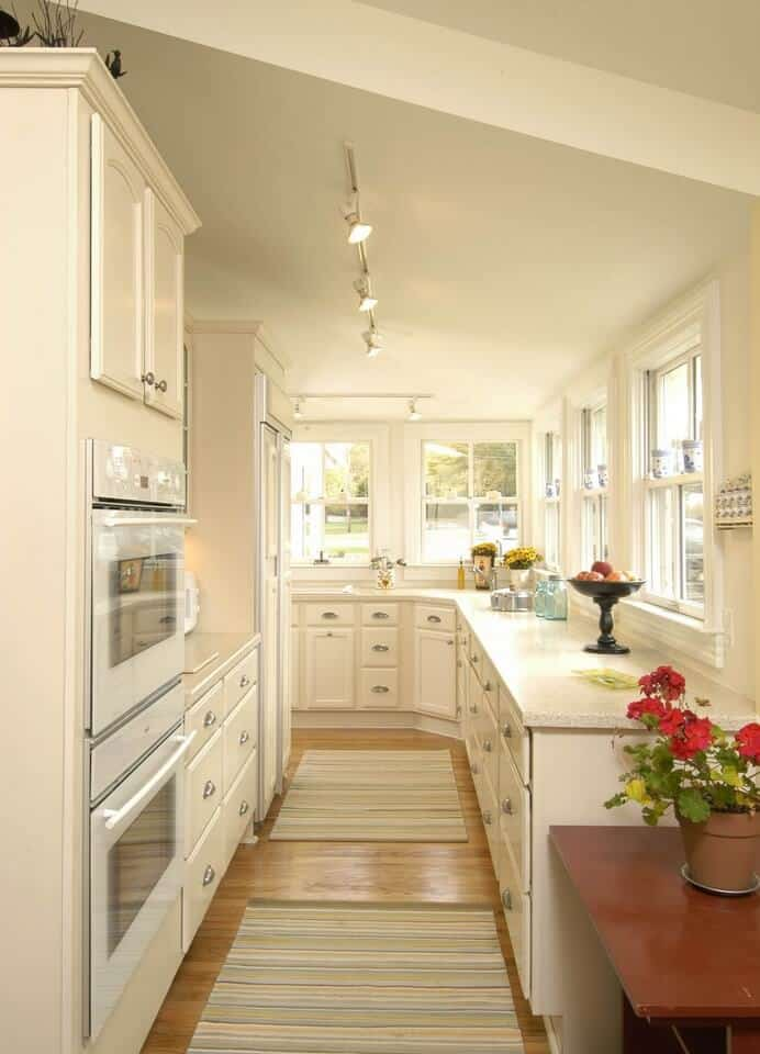 Traditional kitchen with white double wall oven fixed beside the cream cabinetry. It has shed ceiling mounted with track lights and hardwood flooring topped with striped runners.