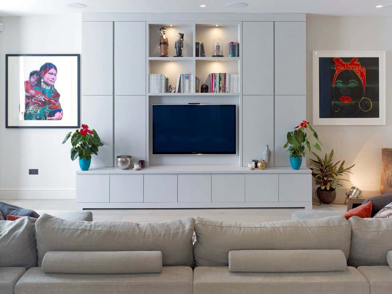 White living room with a gray sofa that faces the built-in tv stand with open shelving. It is accented with lovely portraits and potted plants.