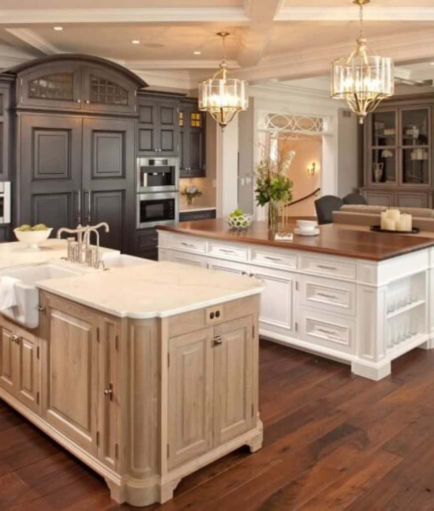 Transitional kitchen features dark wood cabinetry and double kitchen islands illuminated by a pair of drum chandeliers that hung from the coffered ceiling.