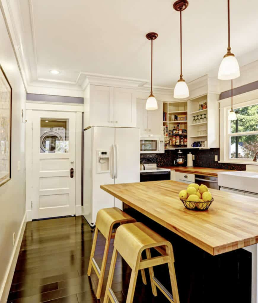 Sleek kitchen with white cabinetry and appliances beautifully contrasted with black wood plank flooring and breakfast island that's topped with a natural wood counter complementing with the bar stools.