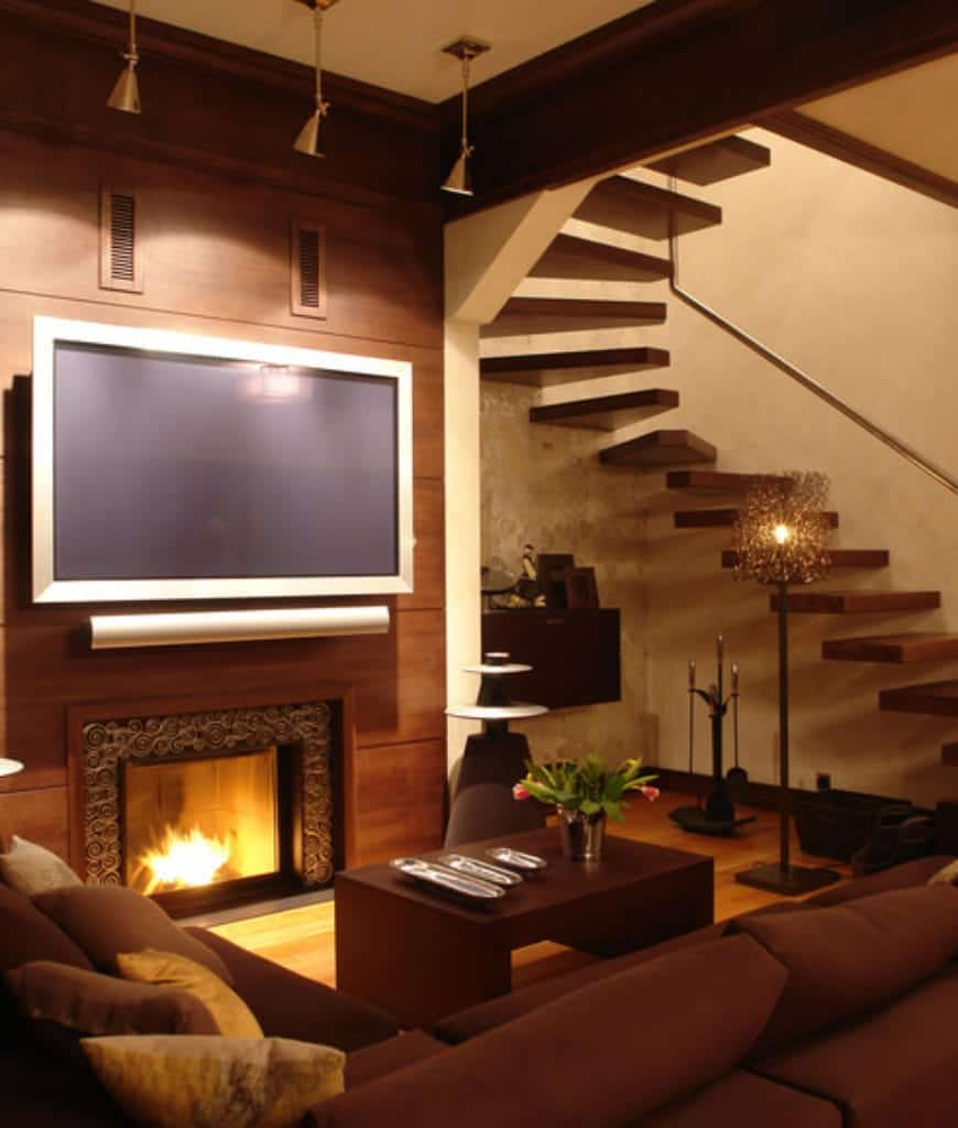 Warm living room features a floating staircase lighted by a fancy floor lamp and a flat panel display that hung above the ornate fireplace.