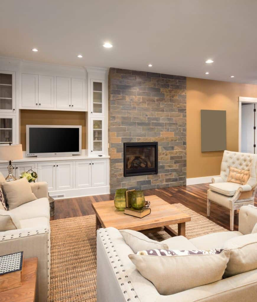 This living room offers a modern fireplace fitted to the brick accent wall next to the built-in white cabinets that are topped with a gray television in between glass front storages.