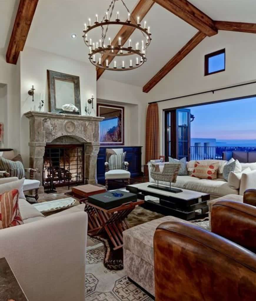 Craftsman living room features wood beam ceiling with a hanging wrought iron chandelier and folding glass door that opens to the balcony. It includes comfy seats and a stone fireplace covered with a metal screen.