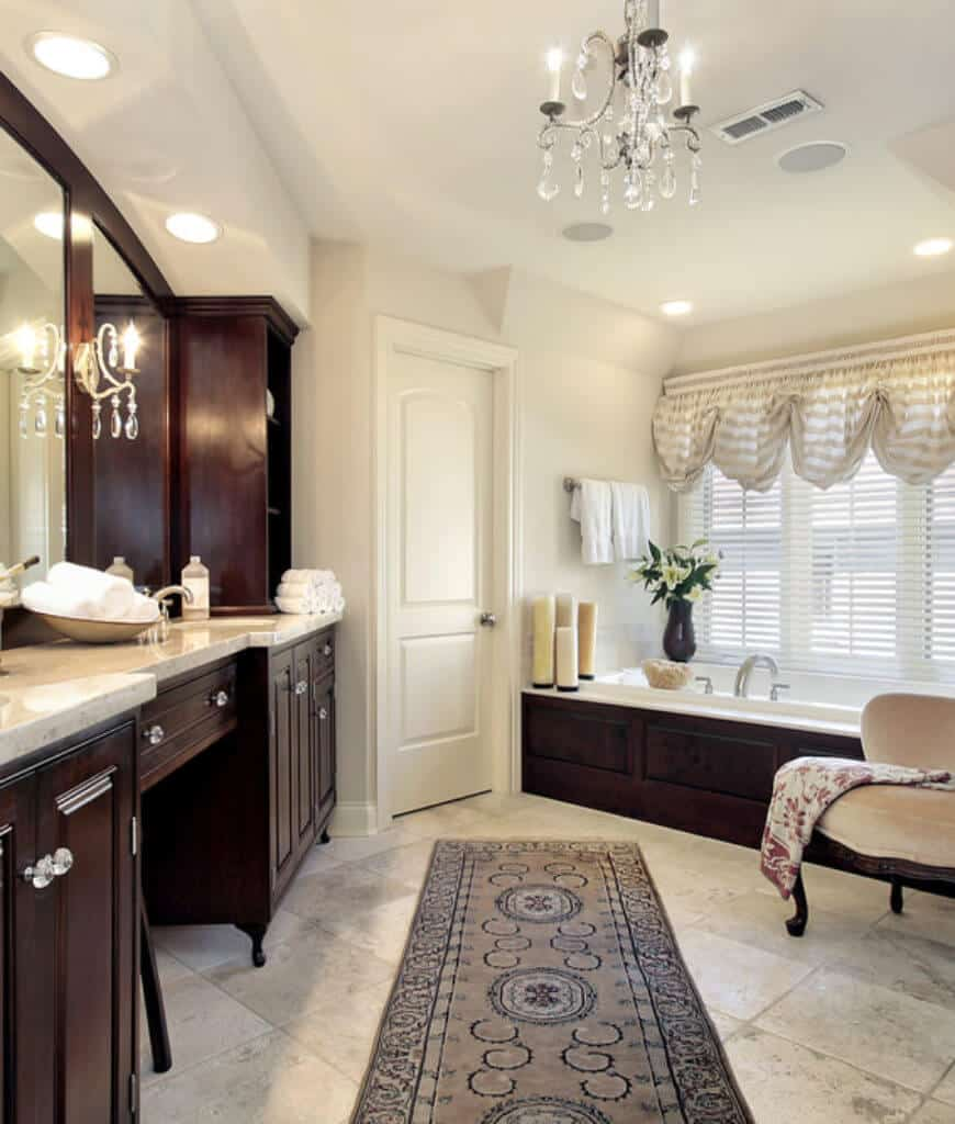 A beige cushioned chair sits in front of the soaking tub in this primary bathroom with wooden sink vanity and concrete tiled flooring topped by a bordered runner.