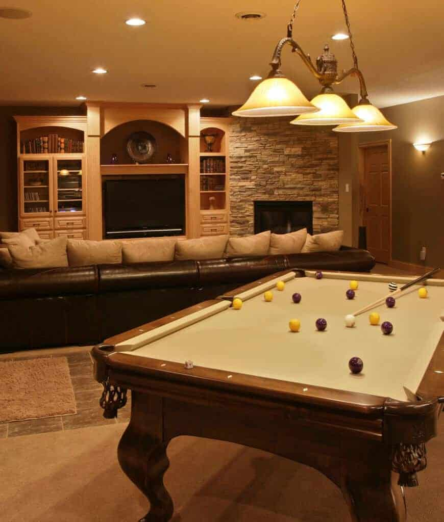 A closeup look at the pool table with yellow and purple balls situated behind the black sectional facing the television and brick fireplace.