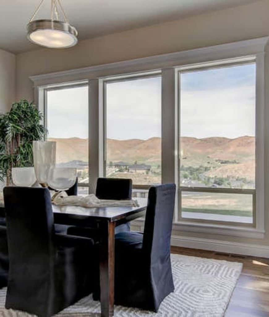 This dining room showcases wood plank flooring and glass paneled windows overlooking a breathtaking mountain view. It has a wooden dining table surrounded with black high back chairs over a gray textured rug.