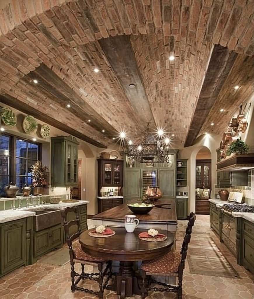Rustic kitchen designed with decorative plates and an ornate chandelier that hung from the barrel vaulted ceiling. It has distressed cabinetry and a wooden central island attached with a curved eating counter over hex tiled flooring.