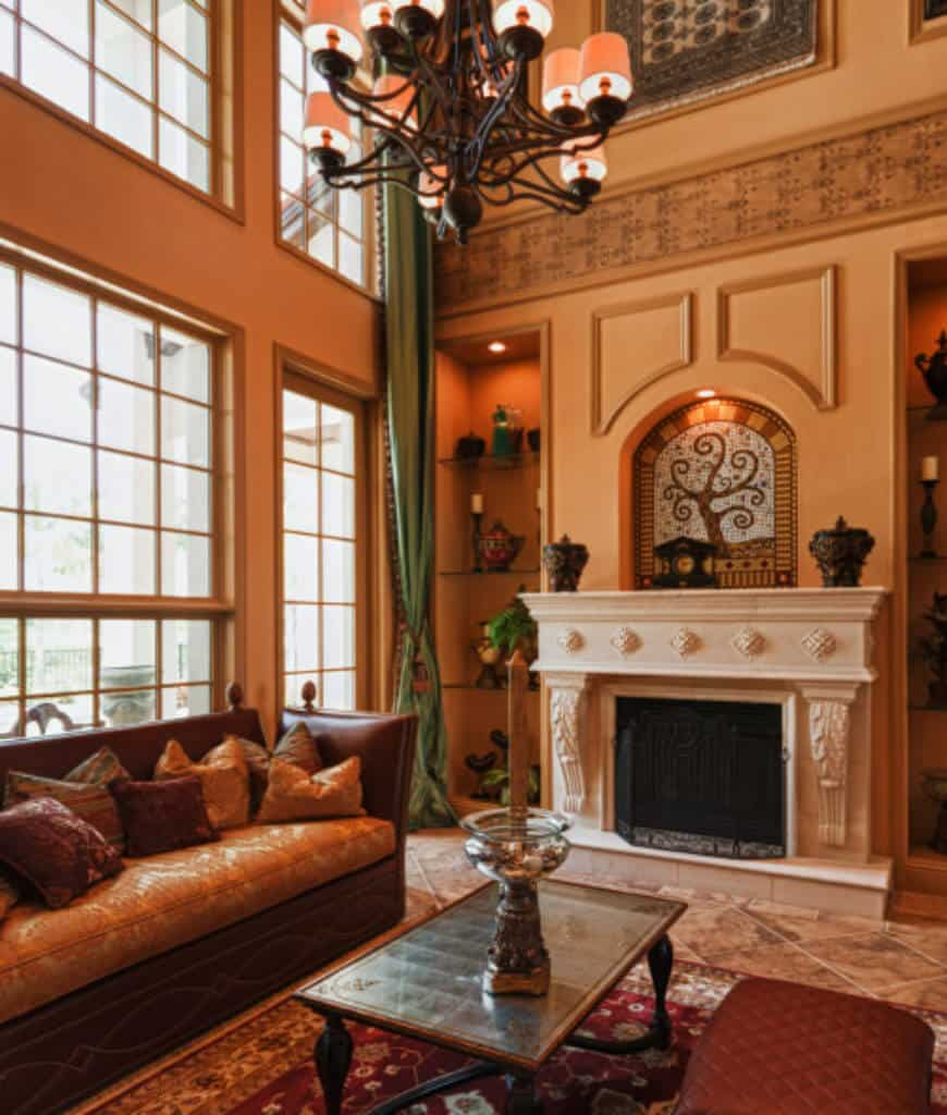 Warm living room with leather sofa and a white ornate fireplace in between inset wall niches fitted with glass shelves. It is illuminated by a vintage chandelier that hung over the coffee table.