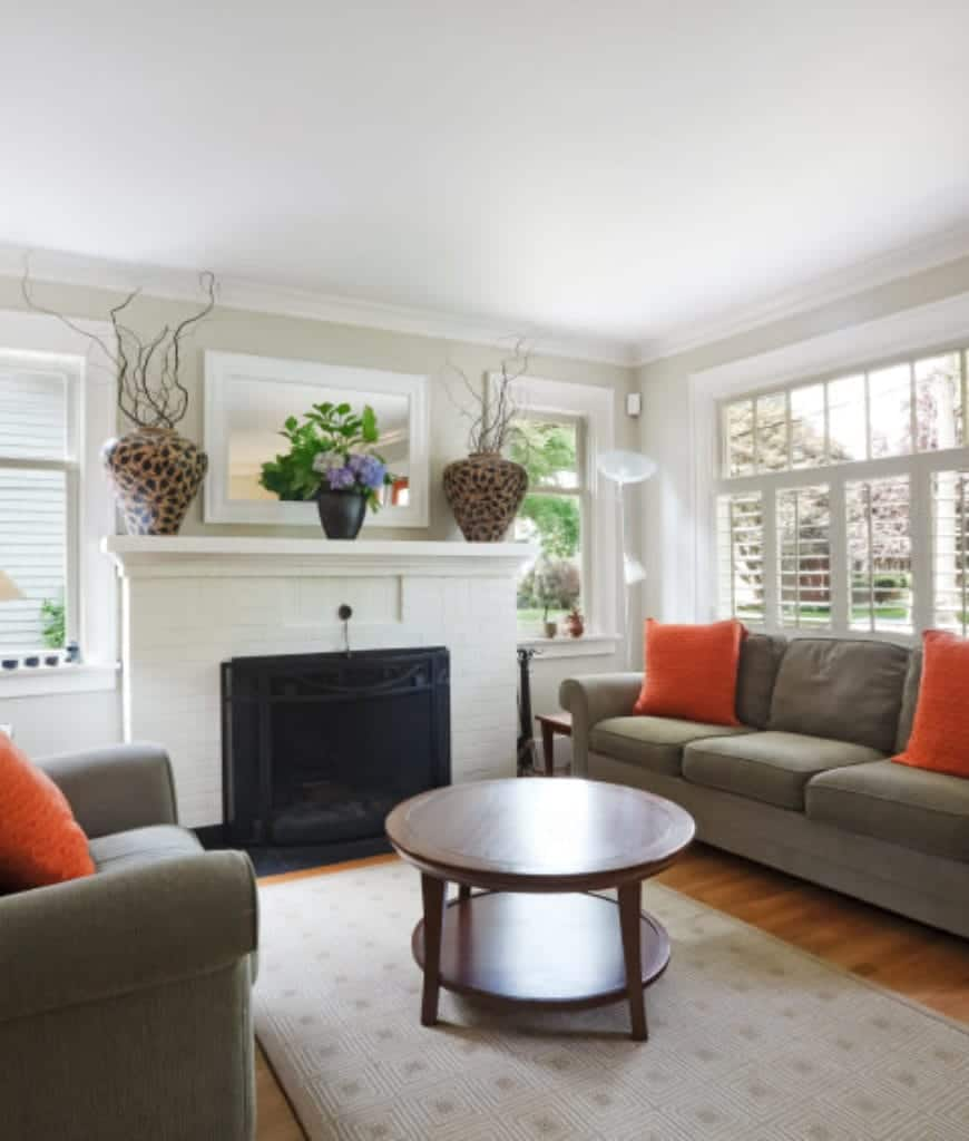 An airy living room with a round coffee table in between gray sectional and armchair accented with bright orange pillows. It includes a fireplace framed with a white mantel that's topped with fabulous vases.